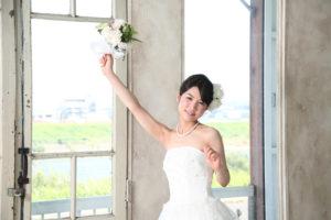 ブーケを持って手を上げる花嫁(結婚)