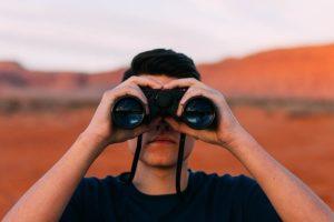 双眼鏡を覗く男性(目を光らせている)