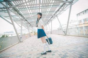 通学鞄を持って立つ女子高校生の全身姿