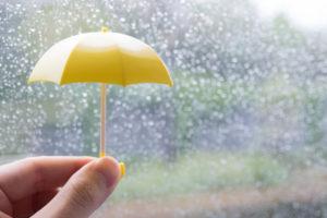 雨の日に小さい黄色の傘を持つ手