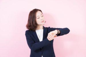 時間を気にして腕時計を見る女性