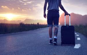 スーツケースを引きながら道路を歩く旅人