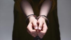 逮捕されて手錠をかけられている女性