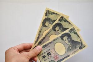 3千円のお金を手に持っている