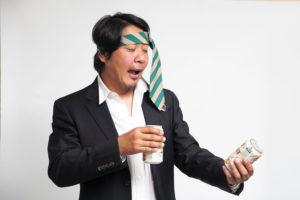 ネクタイを頭に巻く酔っ払いの男性